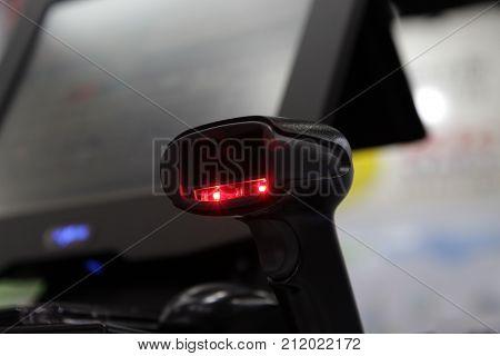 a hand held barcode scanner scanning barcode ; shine red light;destop background