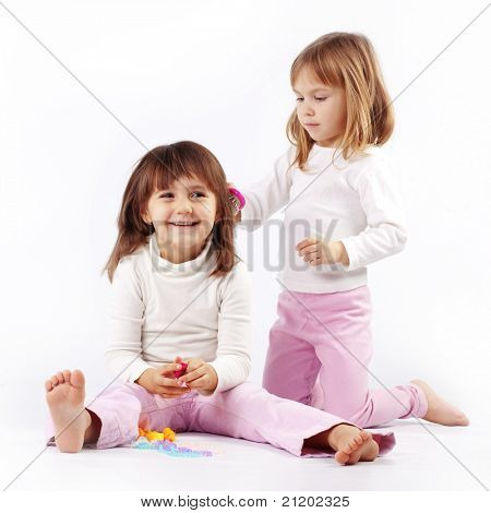 Two little kid girls playing hairdresser