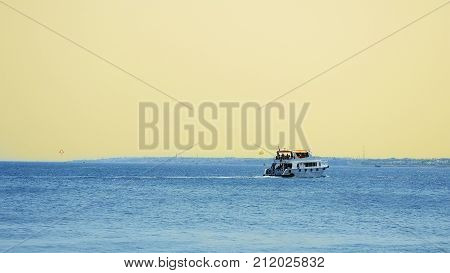 Powerboat ship at sunset is sailing along the tropical seashore. Having a good time in tropical sea or ocean.