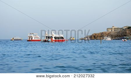 Sharm-El-Sheikh, Egypt - August 27, 2017: Powerboats and touristic ship tourboats are sailing along the tropical resort beach at sunset. Seaside area for vacation and summer relaxation activity.