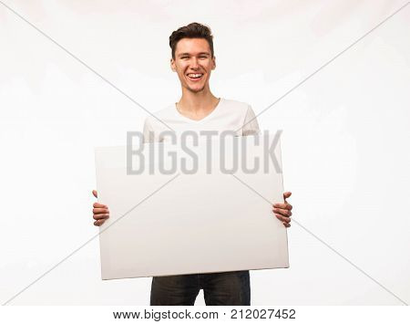 Young cheerful man portrait of a confident businessman showing presentation, pointing paper placard gray background. Ideal for banners, registration forms, presentation, landings, presenting concept.