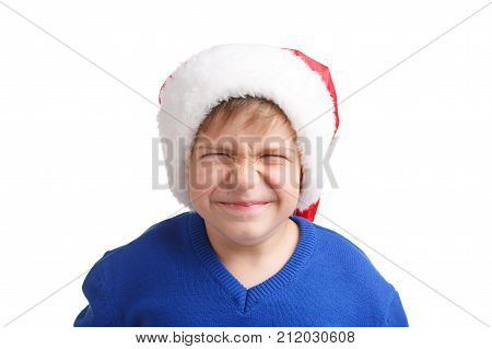 The boy squeezed his eyes in the New Year's cap and blue sweater on a white isolated