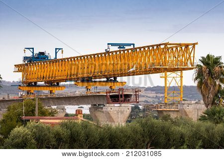 Motorway or autostrada bridge construction with large gantry crane lifting in road sections between pillars. Sicily Italy