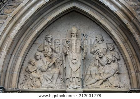 stonework depiction of st.patrick and followers above church door