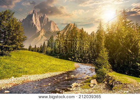 fairy tale mountainous summer landscape at sunset. composite image with high rocky peaks above the mountain river in spruce forest