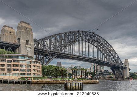 Sydney Australia - March 22 2017: Full frontal of Harbour bridge under heavy dark rainy sky. Luna attraction park and Kirribilly high rises visible under bridge.