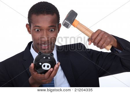 Man in a suit hammering open a child's piggy bank