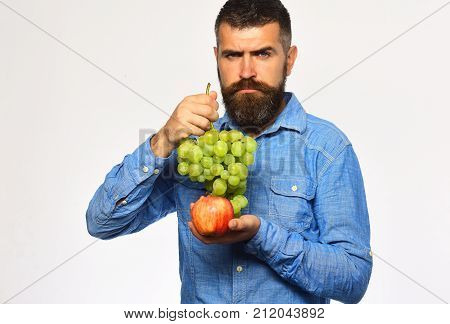 Winegrower With Strict Face Holds Grapes And Red Fruit.