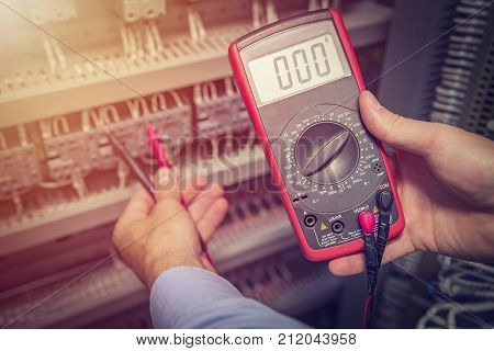 Service engineer with multimeter tester in hands close up. Electrical measurements in electric cabinet. Support specialist with test device.
