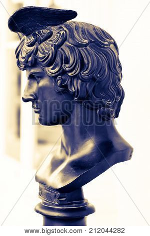 Ancient male statue of Mercury of 18th century outdoor in park. Greek god Hermes bust. Beautiful bronze face closely. God of speed for design, posters, prints, art calendar, cards. Boy