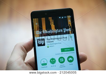 Los Angeles, november 2, 2017: Man hand holding smartphone with The Washington post application in google play store
