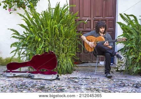 Cordoba Spain - Jun 4 2011: street musician plays the guitar at traditional enclosed courtyard of Cordoba Spain