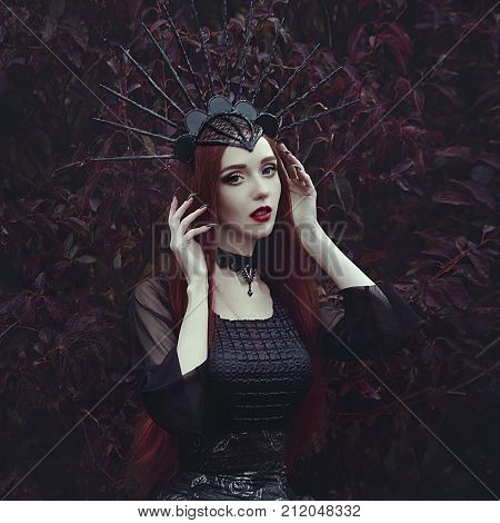 A beautiful woman with pale skin and long red hair in a black dress and in the black crownk. Girl witch with vampire claws and red lips. Gothic look. Outfit for halloween. Creative colors and Artistic processing.