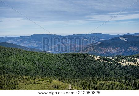 mountains and forests against the background of the day blue sky
