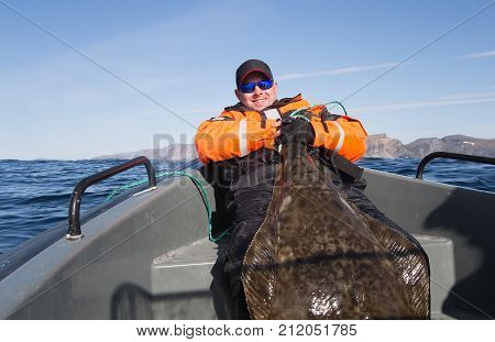 Fisherman holding the tail of a huge fish. horizontal frame