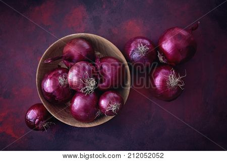 Red onions in a wooden bowl. Food Ingredients.
