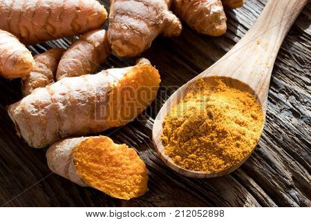 Ground Turmeric On A Wooden Spoon, With Fresh Turmeric Root In The Background