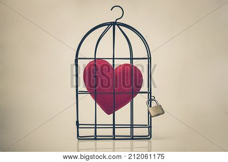 A bird cage with a red heart inside