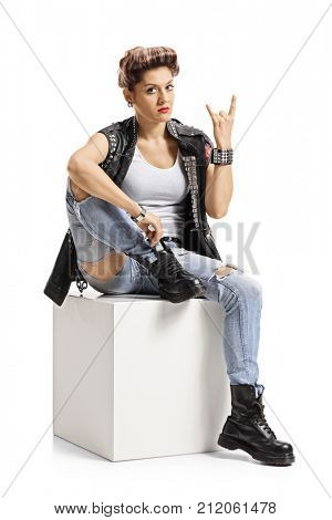 Punk girl sitting on a cube and making a rock hand gesture isolated on white background