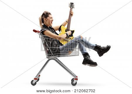 Punk girl sitting inside a shopping cart and playing an electric guitar isolated on white background