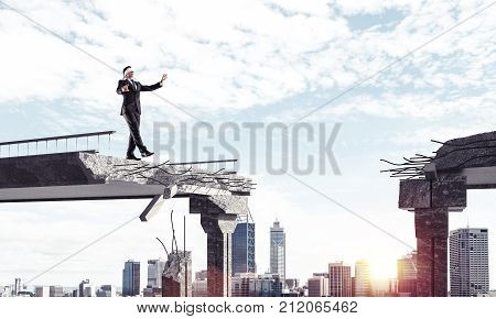 Businessman walking blindfolded on concrete bridge with huge gap as symbol of hidden threats and risks. Cityscape and sunlight on background. 3D rendering.