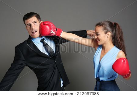 Woman in formal clothes and boxing gloves hitting businessman on grey background