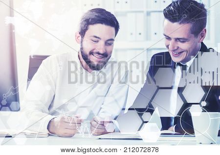 Two young business partners are working together while sitting at their table in a white office. Toned image double exposure