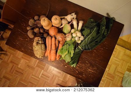 Shot from above of fresh vegetables on table. Carrot, celeriac, butternut squash, kale, turnip, beets