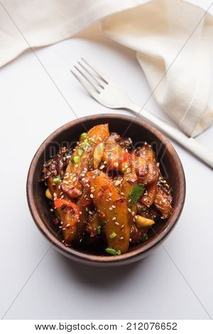honey chilli potato or Potato wedges, popular Indian-Chinese starter recipe, garnished with sesame and onion. selective focus