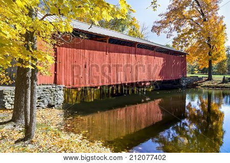 Irishman's Covered Bridge is surrounded by colorful autumn foliage at Fowler Park in Vigo County Indiana.