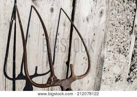 Old broken fork on the background of a wooden fence