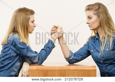Two serious competetive women having arm wrestling fight compete with each other.