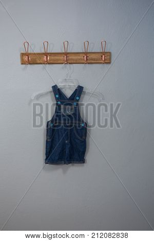 Dungaree hanging on hook against wall