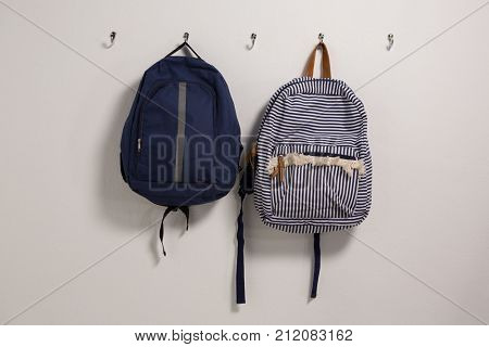 Schoolbags hanging on hook against wall