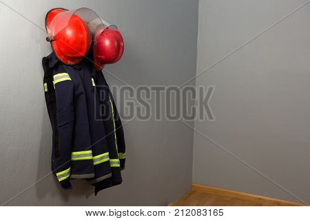 Protective workwear and hard hat hanging on hook against wall