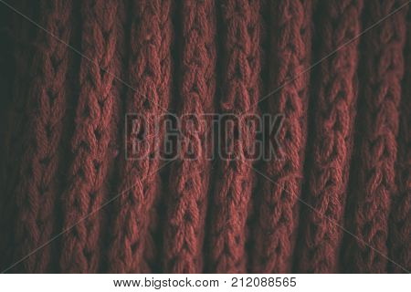 Red vintage knitted fabric texture and background for designers. Vintage knitted background. Close up view of red abstract texture. Dark red vintage cloth.  Dark red knitted pattern.