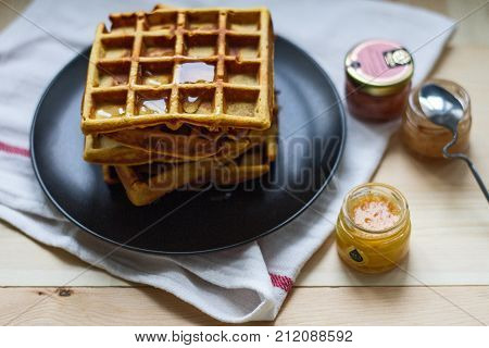 Freshly baked sweet delicious appetizing Belgian waffles made of pumpkin with honey on a black plate on a wooden table.