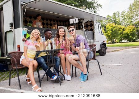 leisure and people concept - happy young friends with food and drinks and taking selfie at food truck