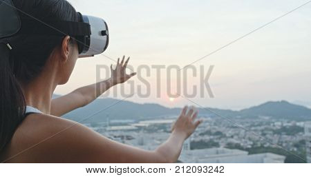 Woman looking at VR device at roof top