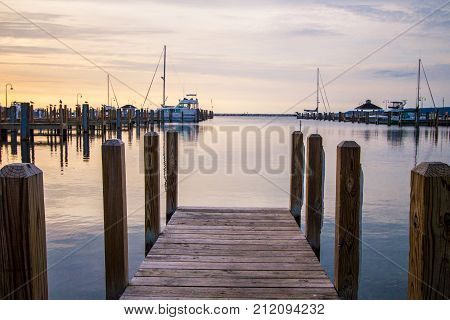 Boater Summer Sunset Over Lake Michigan Harbor.  Wooden dock with a marina and scenic sunset colors at the Great Lakes horizon in Michigan.