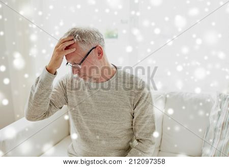 health, stress and people concept - senior man suffering from headache at home over snow