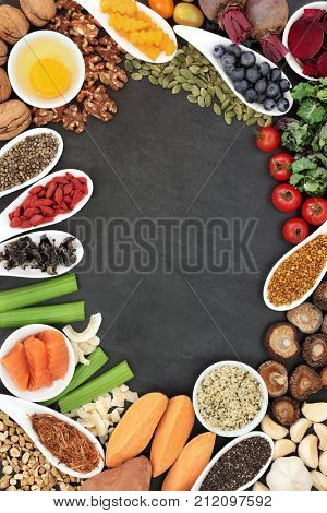 Brain boosting health food background border with fish, vegetables, seeds, nuts,   fruit, herbs and pollen grain on slate. Foods high in omega 3, vitamins, minerals, antioxidants and anthocyanins.