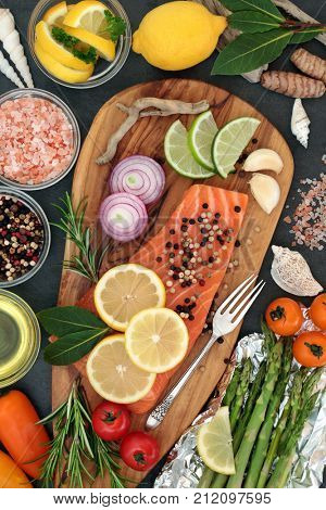 Food to maintain a healthy heart with fresh salmon fish, vegetables, fruit, herbs, seasoning and olive oil on an olive wood board. High in omega 3 fatty acids.