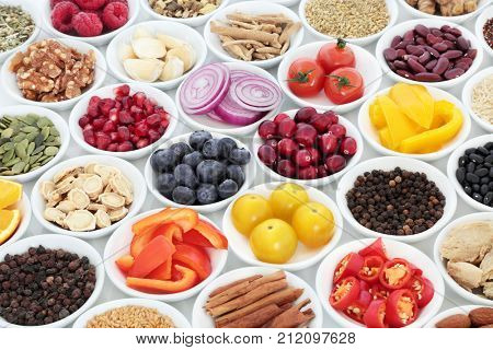 Food for a healthy heart with herbal medicine, vegetables, fruit, pulses, seeds and nuts on white background.  High in omega, antioxidants, anthocyanins, smart carbohydrates and vitamins.