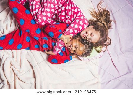 Bedtime slumber dream sleepover. Children in pajamas happy smile in bed top view. Girl nightwear fashion. Comfort home concept. Childhood family love friendship.