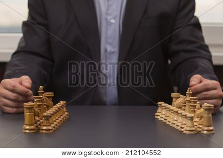 Businessman ponders a strategy of behavior on the market. Chess tournament. Carier start. Chess as an instrument of behavior. The man in the suit is sitting in front of the staggered chess pieces.