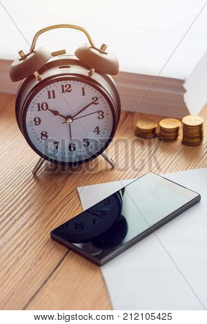 Working hours vintage clock and mobile phone on business office desk
