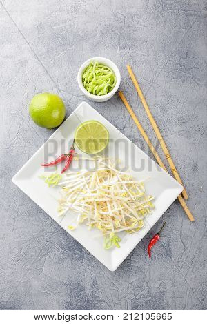 Fresh bean sprouts on white square plate and chopsticks. Concept of healthy foods vegetarian food. Top view