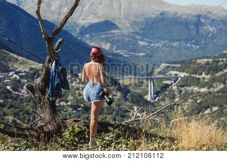 Young naked female photographer with professional camera near big old tree opposite greek village. A girl with camera opposite the village of Metsovo in Greece.