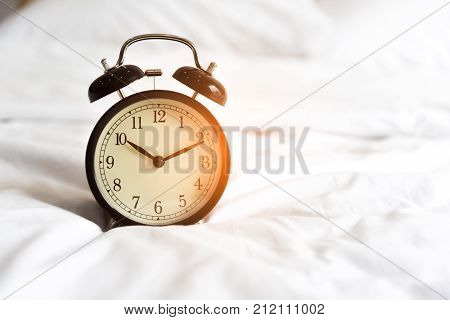 Alarm clock on the white bed. Holiday and reminder concept. Clock hand point to 10 o'clock 10 minute time